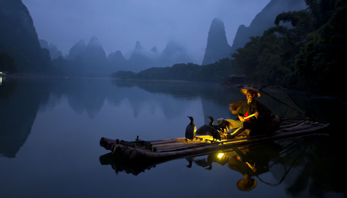China - Fisherman and osprey in Guilin China.
